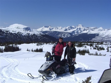 Father and son standing by snowmobile
