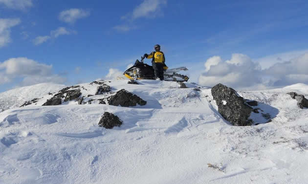 A rider in a yellow jacket sits on his snowmobile at the top of a snowy crest. A dramatic blue sky contrasts the snow and gray rocks.