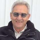 Head-shot of smiling, grey-haired man wearing sunglasses, open-necked white shirt and black winter coat