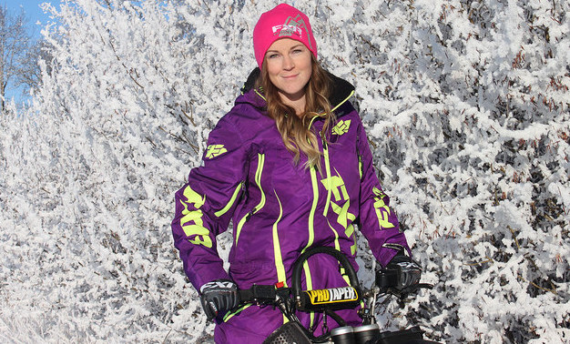 Megan Render, wearing a purple snowmobilers jacket and touque is standing in front of a snow covered bush on a sunny day.