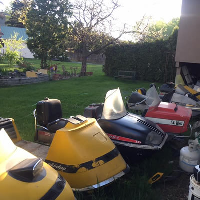 A backyard full of snowmobiles.