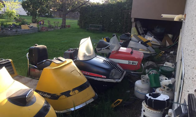 A backyard full of snowmobiles.