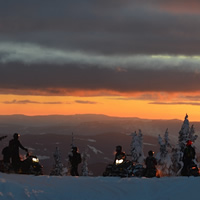 Six sledders on a ridge, against a sunset sky