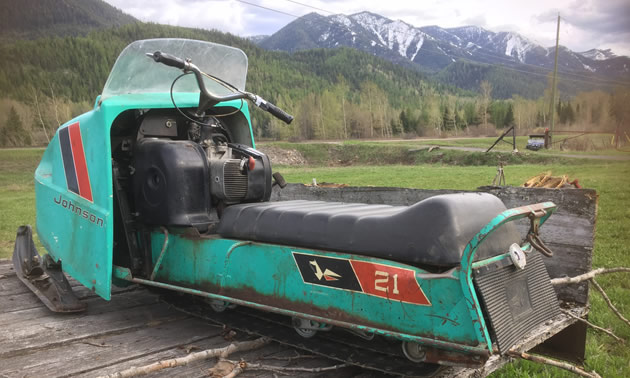 A classic Johnson snowmobile, Model 21, with view of mountains in background.