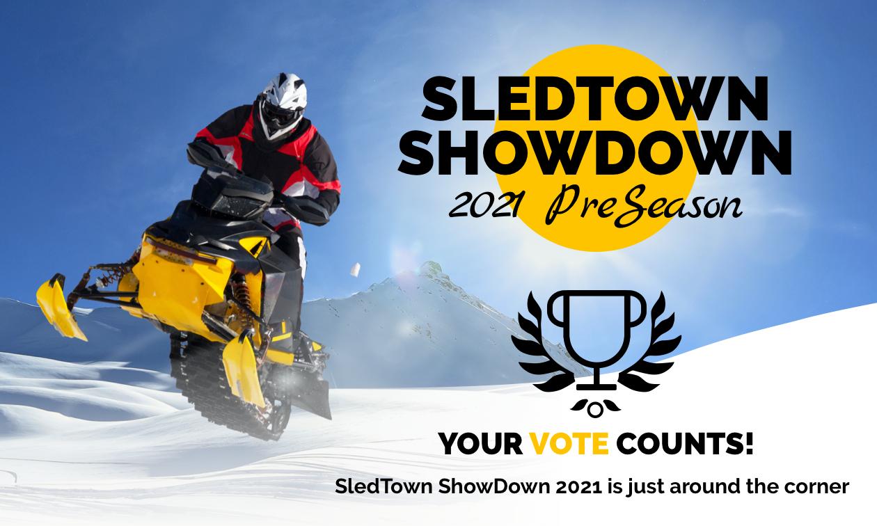 A snowmobiler gets air in the sunshine.