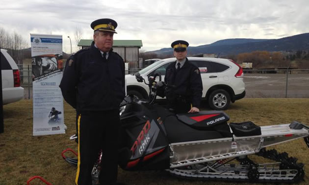 Two RCMP officers stand beside a bait sled.