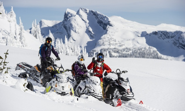 3 riders sitting on their sleds in a mountain bowl near Revelstoke, B.C.