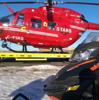 A STARS helicopter with a snowmobile in the foreground.