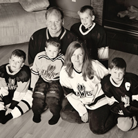 Black and white photo of a man, woman and four young boys—all wearing hockey jerseys—sit on the floor in front of a fireplace