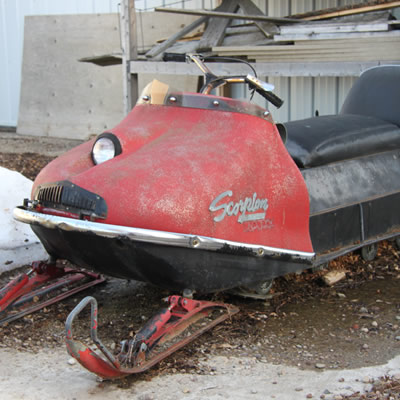 A red vintage Scorpion Trail-A-Sled snowmobile.