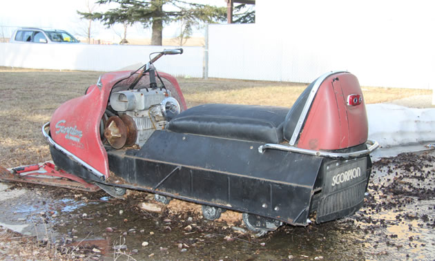 A red vintage Scorpion Trail-A-Sled snowmobile, view from rear.