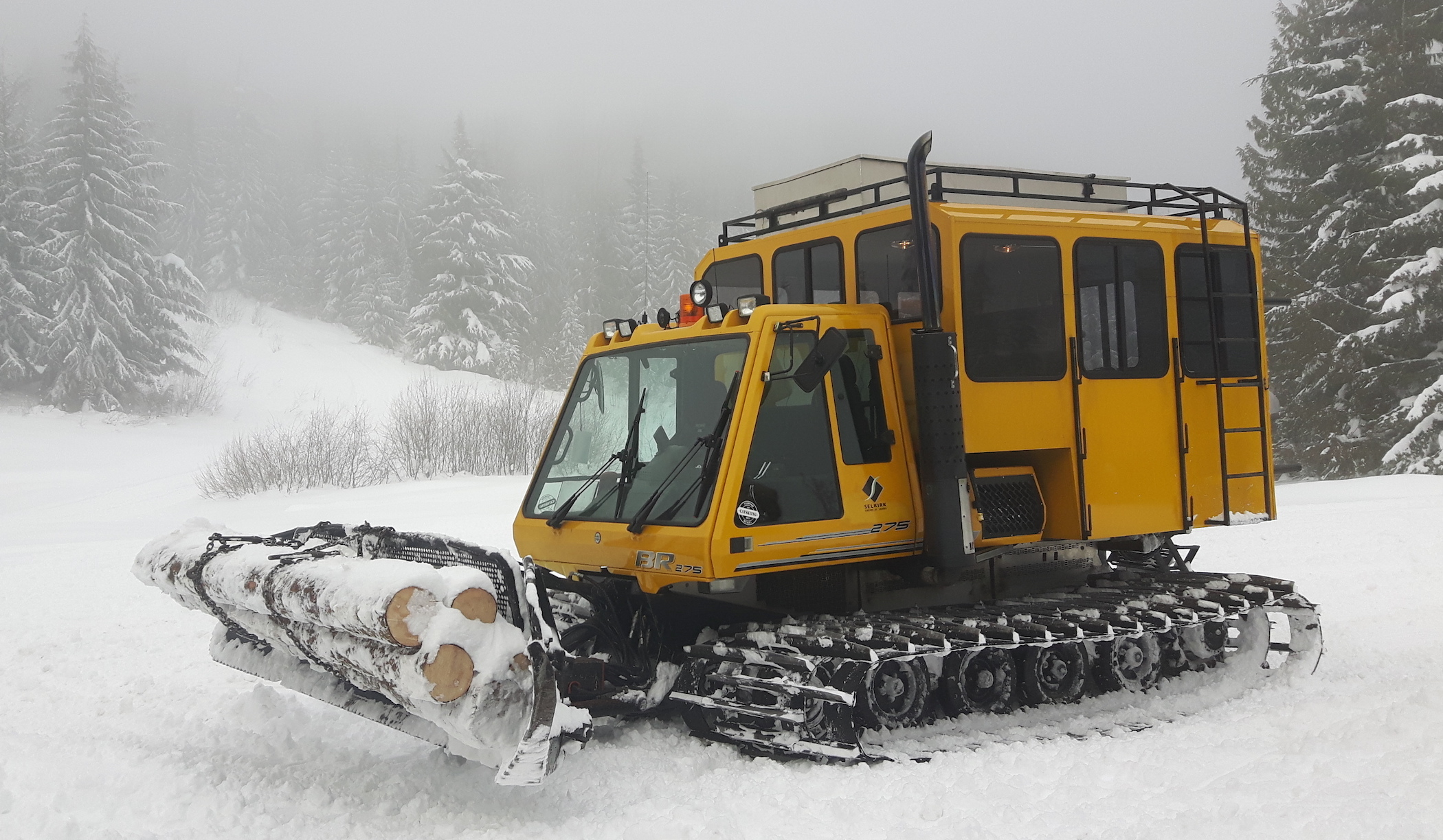 A snowcat is bringing firewood into a backcountry cabin, a good-faith move to help users share the backcountry.