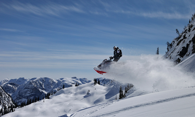 A sledder is air born, leaving a stream of powder behind against a blue sky and an array of mountains.
