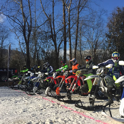 Line-up of kids on snowmobiles at start line of race.