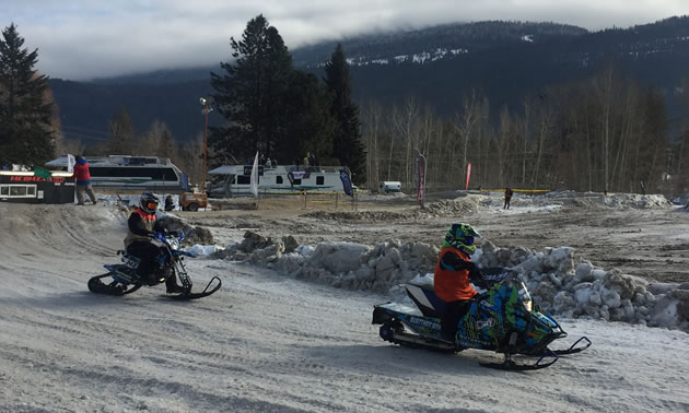 Two kids on snowmobiles racing on track.