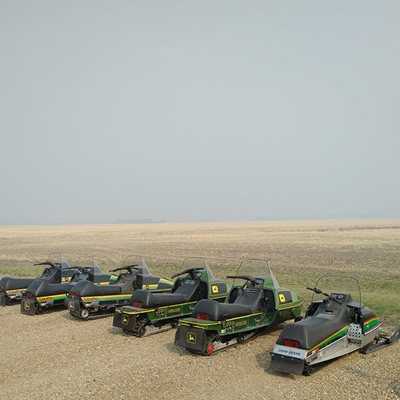 A row of John Deere snowmobiles out in a flat prairie field.