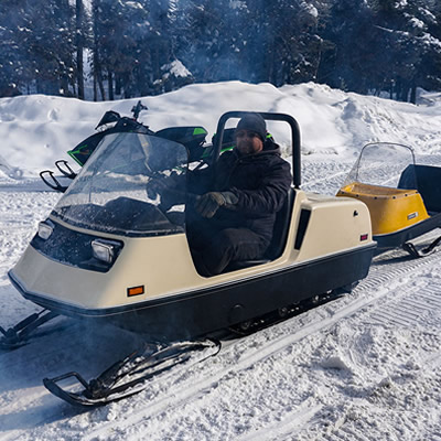 A Ski-Doo Elite, towing a cutter behind it.