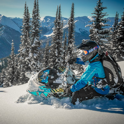Snowmobiler dressed in blue, sledding on slope with snow-covered mountains in background.