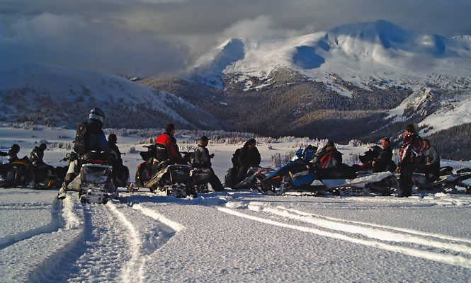 a group of snowmobilers pause in the mountains