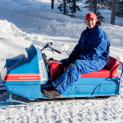 Person sitting on a Snow Cruiser sled.