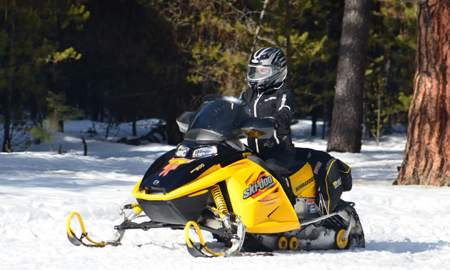 A snowmobiler on a yellow snowmobile.