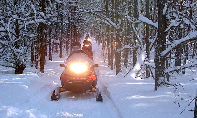 Snowmobiles travel down the Iron Horse Trail near St. Paul, Alberta