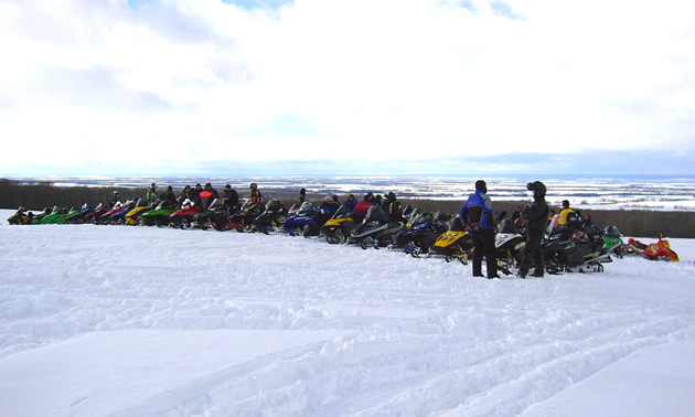 A line-up of sledders are parked on a ridge near Swan River, Manitoba.