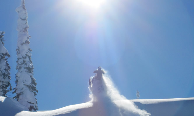 man riding a sled over a hill with sun in the background