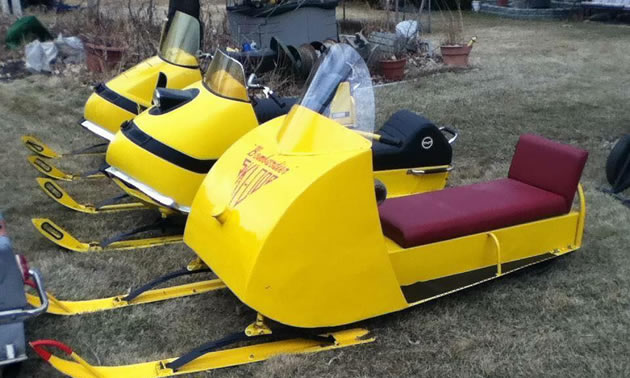 Line-up of yellow snowmobiles.