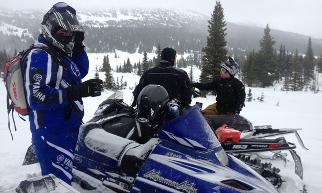 A man dressed in a blue snowsuit and helmet looks at the camera while, behind him, two other riders observe the snowy backdrop.