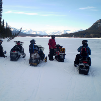 Five snowmobilers sitting on a lake looking out at the Rocky Mountains in the distance.
