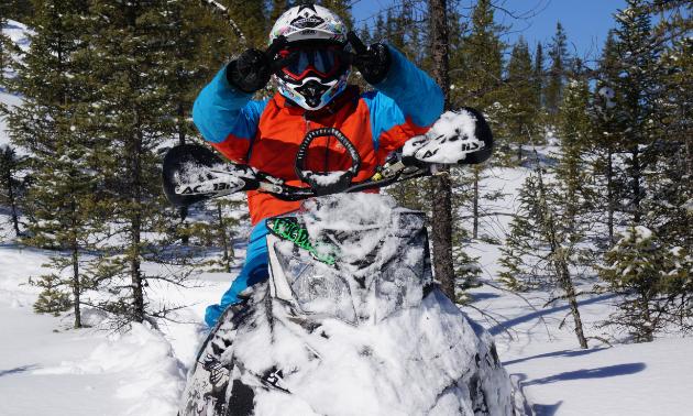 Dargis is riding a snowmobile through trees.