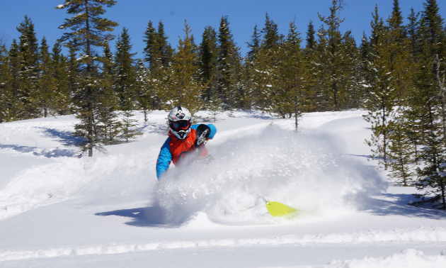 Eric Dargis is riding his snowmobile in powder.