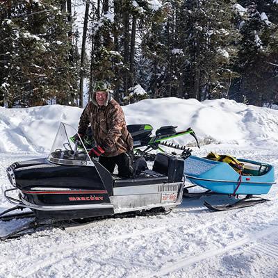 Mercury 250 snowmobile on snowy trail with blue Snoboggan being towed behind it.