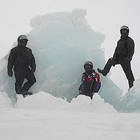 Three men next to an iceberg