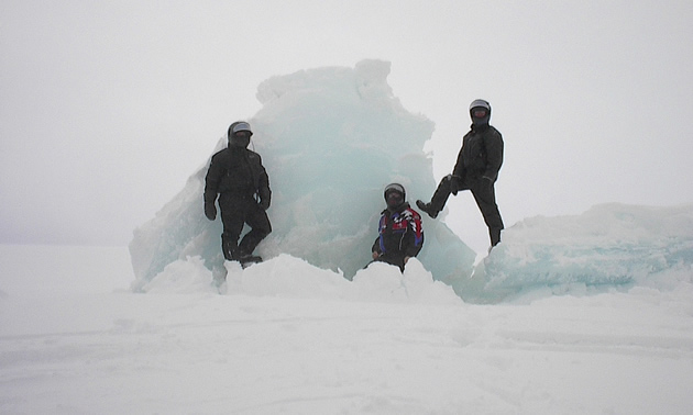 Three men next to an iceberg