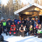 Crowd of 50 or more happy-looking people gather outside a warm-up cabin on a sunny winter day