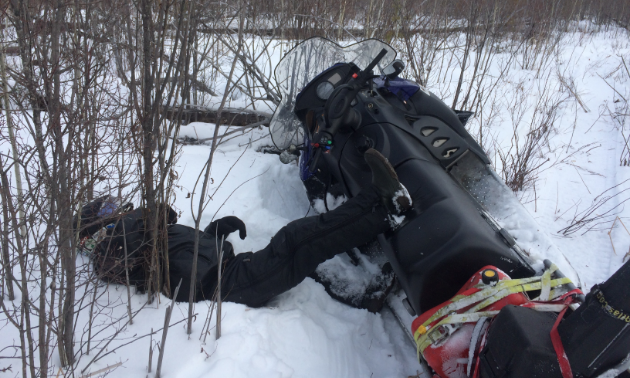 Man fell over on snowmobile.