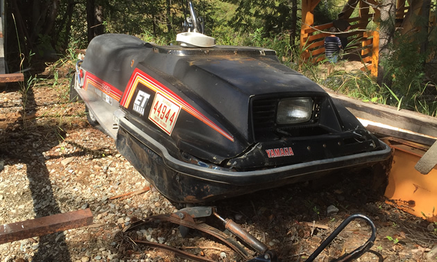 Picture of rusting snowmobile in backyard.