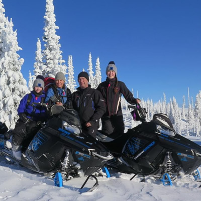 Group of snowmobilers at top of mountain with blue sky in background.