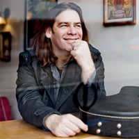 Alan Doyle's profile picture with guitar.
