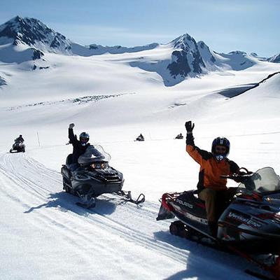 A group of Alaskan snowmobilers riding down a snowy mountain trail.