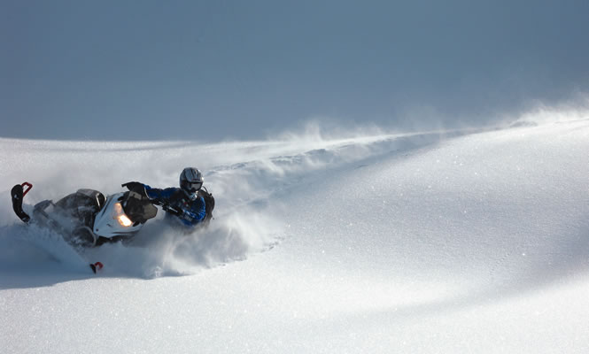 a snowmobiler carves a path on a gentle snow-covered slope