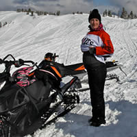 A pregnant woman in a red and white shirt standing beside her sled.