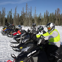 Snowmobilers lined up in a row, ready to ride.