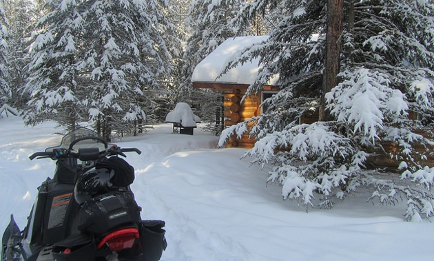 """The Cabin"" under a large dump of new powder snow, on the South West end of the Bilsky Loop, about 7km off of the Trans Canada Snowmobile Trail."