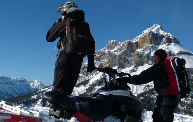 two snowmobilers looking at the mountains.