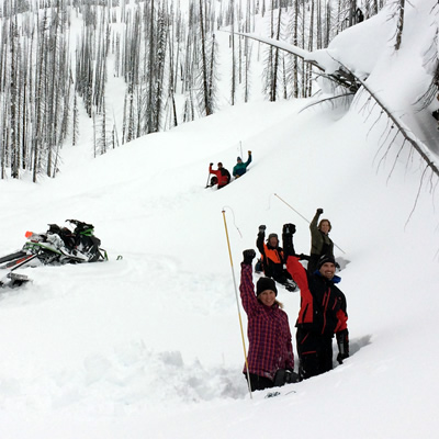 A group of AST students digging a snow pit.