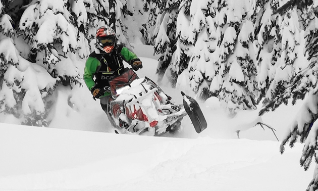 A woman carving through the snow on her snowmobile.