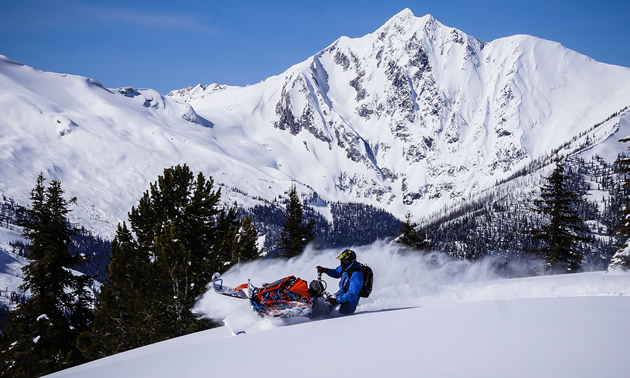 Cody Lumax carving snow with mountains in the backdrop.